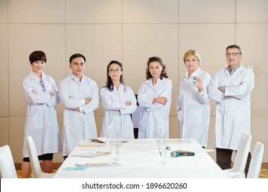 International group of scientists in labcoats standing in conference room after discussing advantages of new coronavirus vaccine