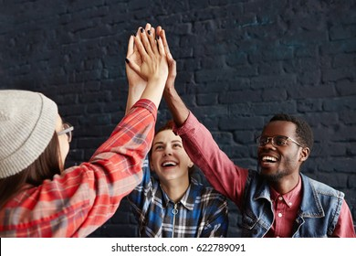 International group of stylish young students giving high five at cafe while having lunch, celebrating successful examination at college. Education, success, teamwork, achievement and cooperation