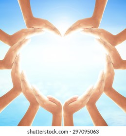 International human rights day concept: Human hands in shape of heart on blurred sun light and blue sky with ocean background