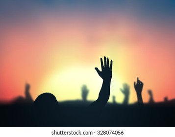 International human rights day concept: Silhouette people hands rising over blurred abstract autumn sunset background