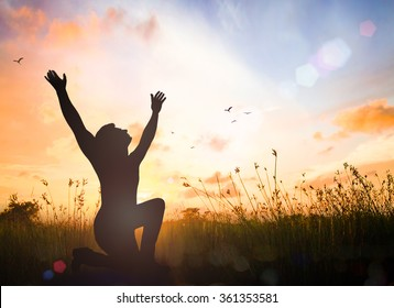 International human rights day concept: Silhouette humble people  kneeling and raising hands for pray to God on meadow sunset background