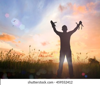 International human rights day concept: Silhouette human hand holding gold medal and broken chains against twilight sky