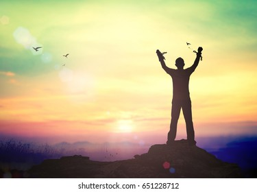 International human rights day concept: Silhouette human hand holding gold medal and broken chains against twilight sky.