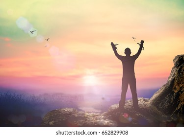 International human rights day concept: Silhouette human hand broken chains against twilight sky background