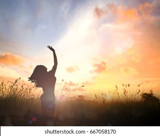 International human rights day concept: Silhouette of beautiful woman kneeling and raised hands for thank you God on autumn sunset background