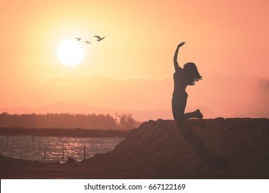 International human rights day concept: Silhouette of christian woman kneeling and raised hands for worship God on beach autumn sunset background