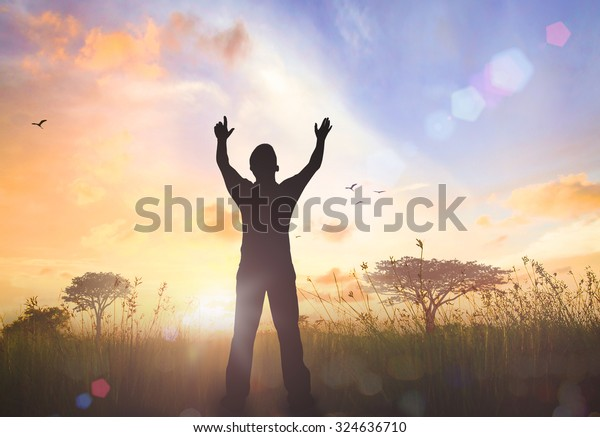 International human rights day concept: Human raised hands for praying God on autumn sunset background