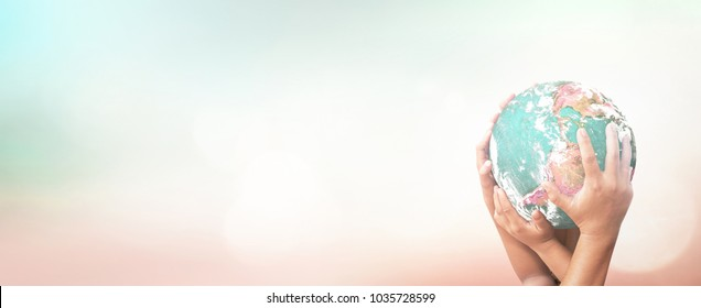 International human solidarity day concept: Many human hands holding earth globe over blurred nature background. Elements of this image furnished by NASA