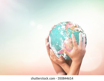 International human solidarity day concept: Children hands holding earth globe over blurred abstract nature background. Elements of this image furnished by NASA