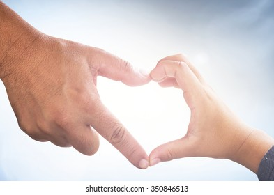 International human solidarity day concept: Father and son hands forming shape of heart on blurred sunshine blue sky background