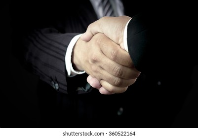 International human solidarity day concept: Two successful businessmen shaking hands after good deal