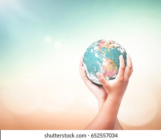 International human solidarity day concept: Child hands hold earth globe over blurred abstract nature background. Elements of this image furnished by NASA
