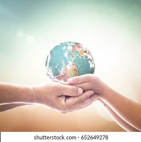 International human solidarity day concept: Children hands holding earth global over blurred abstract nature background. Elements of this image furnished by NASA