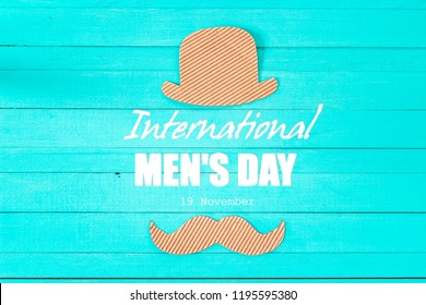 International men's day background with cardboard hat and mustache on blue  backdrop.