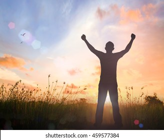 International migrants day concept: Silhouette of man raised hands at meadow autumn sunset background