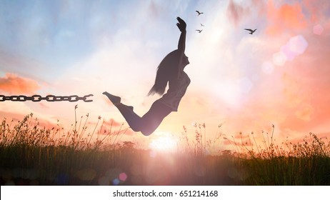 International migrants day concept: Silhouette of a girl jumping and broken chains at sunset meadow with her hands raised