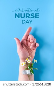 International nurse day. Hand of mature woman with chamomile flower bouquet attached with medical aid patch. Creative modern flat lay, top view on blue background.