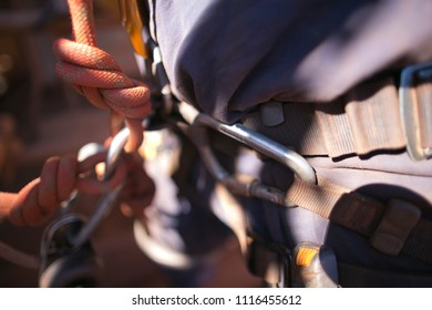 International rope access maintenance worker using carabiner connecting clipping his seat into harness abseiling safety loop ready to work at construction work site, mining Perth city, Australia