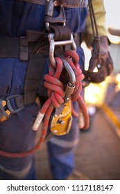 International rope access miner worker having his ascender clipping on the  harness abseiling safety loop along with back up devise cow tails at construction  work site, mining Perth city, Australia