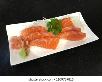 International Sushi Day, Raw salmon slice of salmon in Japanese style serve in a white plate with fresh wasabi On a black background in indoor low lighting.