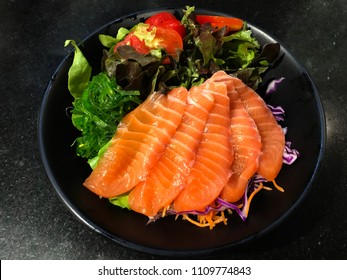 International Sushi Day, Raw salmon slice of salmon Salad in Japanese style serve in a black plate  On a black background in indoor low lighting.