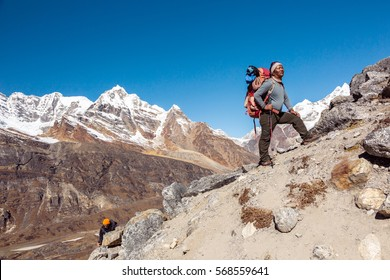 International Team of Mountain Climbers ascending Himalaya Summit led by iconic Nepalese Sherpa Guide staying with Backpack and alpine Gear and planning further Route