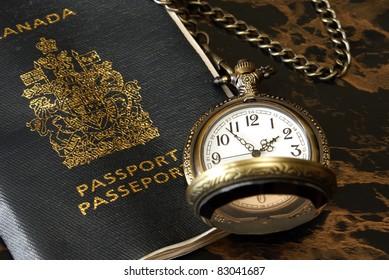 An international traveler has a passport and pocket watch ready.