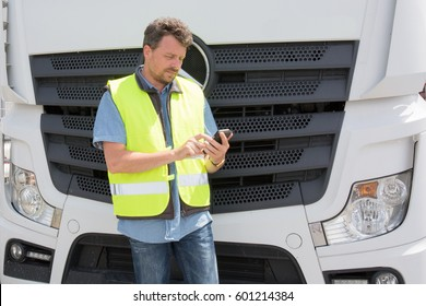 international truck driver in front of his truck with his mobile phone and his yellow safety vest