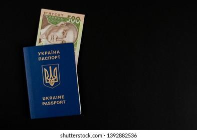 International ukrainian passport and 500 hryvnas on black background. Copy space. Finance and migration concept.