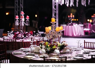 International Wedding outdoor celebration EVENING party under palm trees. Served tables on green area in hotel. Landyard. Beige and pink colors. Candles stand on tables