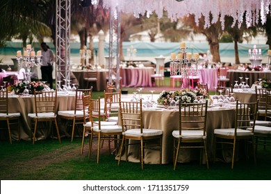 International Wedding outdoor celebration EVENING party under palm trees. Served tables on green area in hotel. Landyard. Beige and pink colors. Close-up and wide angle.