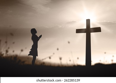 International women day concept: Silhouette woman prayer is praying over cross on spiritual light background.