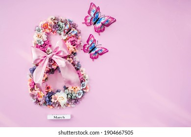 International Women's Day. Banner, flyer, beautiful postcard for March 8. Flowers and butterflies in the shape of the number 8 on a pink background. - Shutterstock ID 1904667505