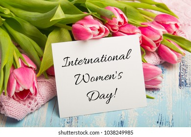 International Women's Day. card Pink tulip bouquet and balnk paper on blue wooden background. Beautiful flowers