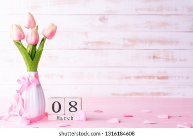 International Womens day concept. Pink tulips and red heart with March 8 text on wooden block calendar on white wooden background.