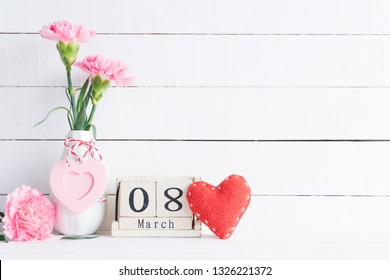 International Womens day concept. Pink carnation flower in vase and red heart with March 8 text on wooden block calendar on white wooden background.