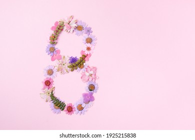 International Women's Day. Flowers in the shape of the number 8 on a pink background.