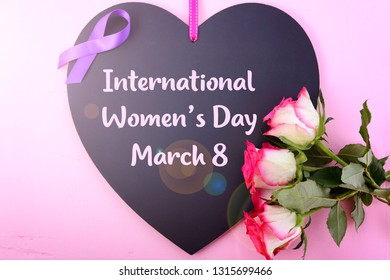 International Women's Day, March 8, heart shaped blackboard greeting with purple ribbon symbol and pink roses on pink wood background with lens flare.