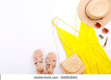 International womens day sale. Woman clothes & accessories, spring summer collection. Yellow dress, straw hat & shoulder bag, brown sunglasses eyewear. Nail polish, lip gloss. Flat lay, background.
