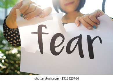 International Women's Day theme hands of woman tearing white paper with fear inscription on blurred background of green plants with bokeh defocused lights in backyard garden /close up, selective focus
