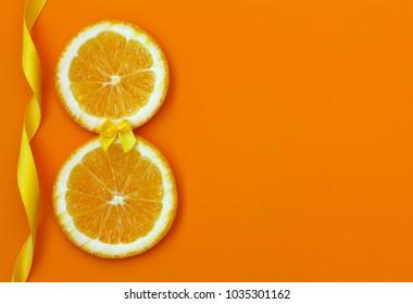 International Women's Day, two slices of orange, silk ribbon on dark yellow textured background