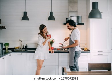 International Women's Day. Young couple in the morning in the kitchen at home. A man cooks a woman a festive breakfast on March 8 in a beautiful stylish kitchen.