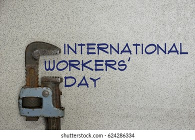 "International Workers' Day concept : May 1, pipe wrench on the concrete floor with the words ""International Workers' Day"""