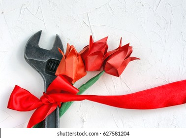 International Workers' Solidarity Day, 1 May concept, wrench with red ribbon and origami tulip on white textured surface