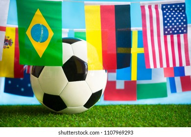 International world flag bunting hanging around a football sitting on grass