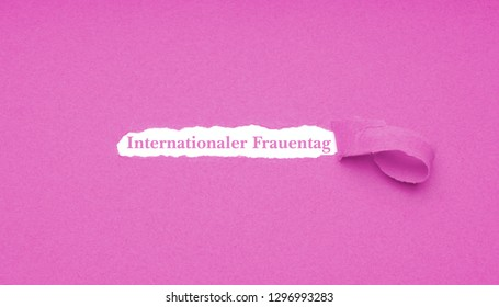 Internationaler Frauentag is German for International Women's Day which is celebrated on March 8 - text revealed by hole torn in pink paper background