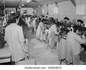 Interned Japanese American, Sumiko Shigematsu, standing at left, supervises fellow internees working at sewing machines at Manzanar Relocation Center, California. 1943 photograph by Ansel Adams.