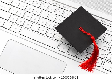 Internet academic learning, e-learning and online college education concept theme with close up on graduation cap with red tassel on computer keyboard with copy space