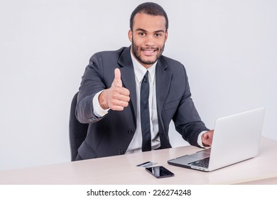 Internet banking for business. Successful African businessman sitting at a laptop and holding credit card in hand until businessman doing orders through the Internet showing a thumbs up