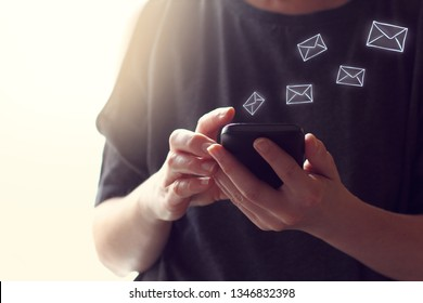 Internet messages in the form of envelopes fly out of the smartphone in their hands. virtual mail program
